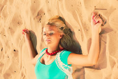 Woman lying on sandy beach relaxing during summer Stock Image