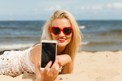 Woman lying on sandy beach using cell phone stock image