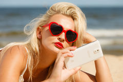 Woman lying on sandy beach using cell phone Royalty Free Stock Image
