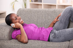 Woman lying on settee Stock Image
