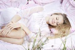 Woman lying on a sheet in field Stock Image
