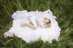 Woman lying on a sheet in field Royalty Free Stock Photos