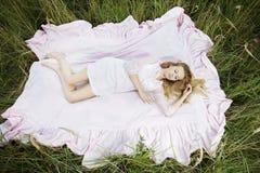 Woman lying on a sheet in field Stock Photo