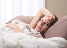 Woman lying sick in bed Royalty Free Stock Images