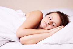 Woman lying and sleep. Beautiful woman lying and sleep on the snowy bed Stock Photos