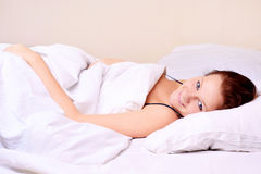 Woman lying and sleep on the snowy bed Royalty Free Stock Images