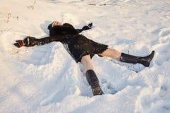 Woman lying in snow Stock Photo
