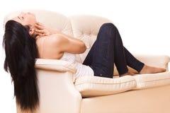 Woman lying on sofa Stock Photos