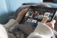 Woman lying on sofa with blanket and choosing a netflix movie on tablet