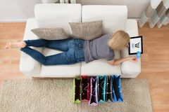 Woman Lying On Sofa With Digital Tablet And Shopping Bags Stock Photos