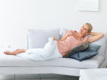 Woman lying on the sofa having coffee , thoughtful Royalty Free Stock Image