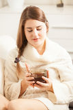 Woman lying on sofa and holding cup of tea Royalty Free Stock Image