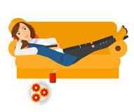 Woman lying on sofa with junk food Stock Photography