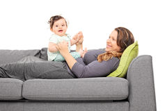 Woman lying on sofa and looking at her daughter Stock Photos