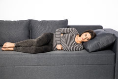 Woman lying on sofa looking sick Stock Images
