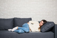 Woman lying on sofa looking sick in the living room Stock Images