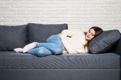 Woman lying on sofa looking sick in the living room Stock Photography