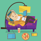 Woman lying on sofa with many gadgets. Royalty Free Stock Images