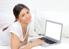 Woman lying on the sofa with modern laptop Stock Images