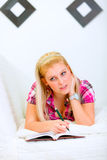 Woman lying on sofa with notebook and pen Stock Images