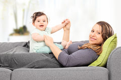 Woman lying on sofa and playing with a baby girl royalty free stock photo