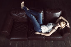 Woman lying on sofa Stock Images