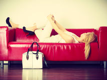 Woman lying on sofa presenting white bag Stock Photos