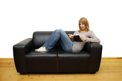 Woman lying on a sofa and reading a book Royalty Free Stock Image