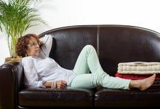 A woman lying on a sofa Stock Image
