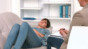 Woman lying on sofa and speaking with psychologist. In office stock video