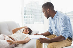 Woman lying on sofa talking to her therapist Royalty Free Stock Image