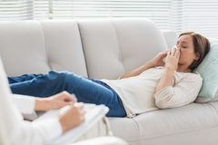 Woman lying on sofa by therapist Royalty Free Stock Images