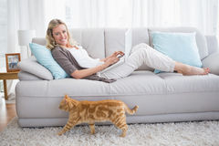Woman lying on sofa using her laptop smiling at camera Royalty Free Stock Images