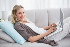 Woman lying on sofa using her laptop smiling at camera Stock Image