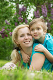 Woman lying with son on green grass Royalty Free Stock Photography