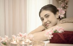 Woman lying on spa bed with flower candles red towel. Woman lying on spa bed with flower candles and red towel Stock Photography