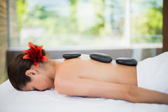 Woman lying with spa stones at her back Stock Image