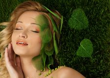 Woman lying on a spring grass Royalty Free Stock Image