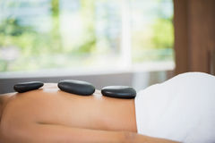 Woman lying on with stones on her back at spa Stock Photography