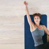 Woman lying and stretching on exercise mat Royalty Free Stock Images