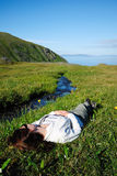 Woman lying supine near stream in green grass Royalty Free Stock Photo