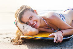 Woman lying on surfboard Royalty Free Stock Image