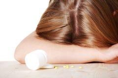 Woman lying on table full of pills Stock Photos