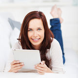 Woman lying with a tablet on a sofa Royalty Free Stock Photos