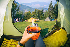 Woman lying in a tent with coffee ,view of camping. With people near the fire and forest royalty free stock photography