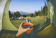 Woman lying in a tent with coffee Royalty Free Stock Photos