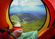 Woman lying in a tent with coffee Stock Image