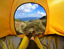 Woman lying in tent with a view of mountain and sky Stock Photos