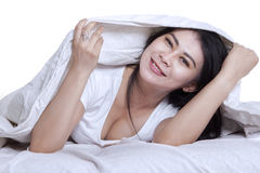 Woman lying under blanket and smiling at camera Stock Images