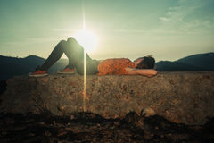 Woman lying on unusual rock at sunrise Royalty Free Stock Photography